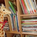 Giraffe mit Kinderbüchern in der Bücherei